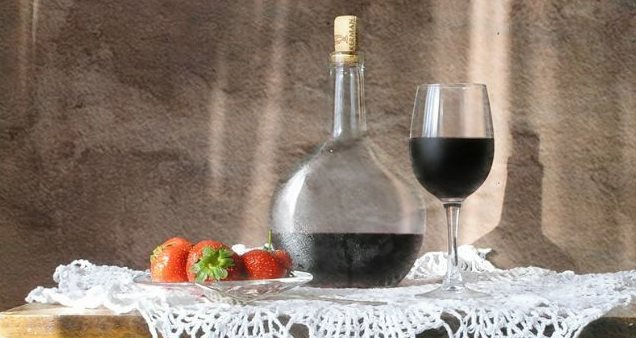 Фото домашнее вино из варенья на столе с клубникой