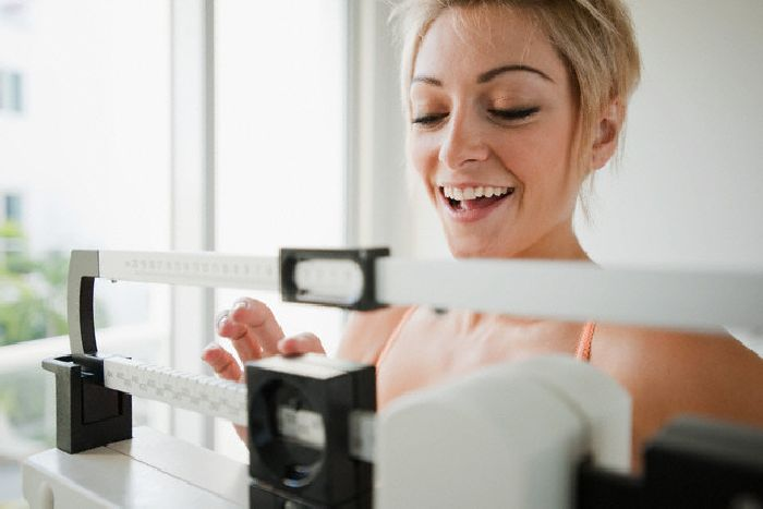 Фото девушки на весах измеряет вес после рекомендаций врача-диетолога с отзывами худеющих