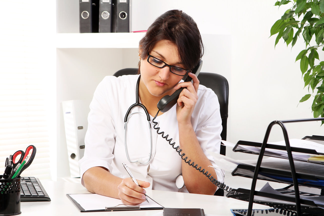 Young woman doctor talking by phone in her office